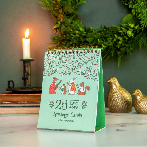 Green 25 days of carols advent calendar sitting on a countertop with candle